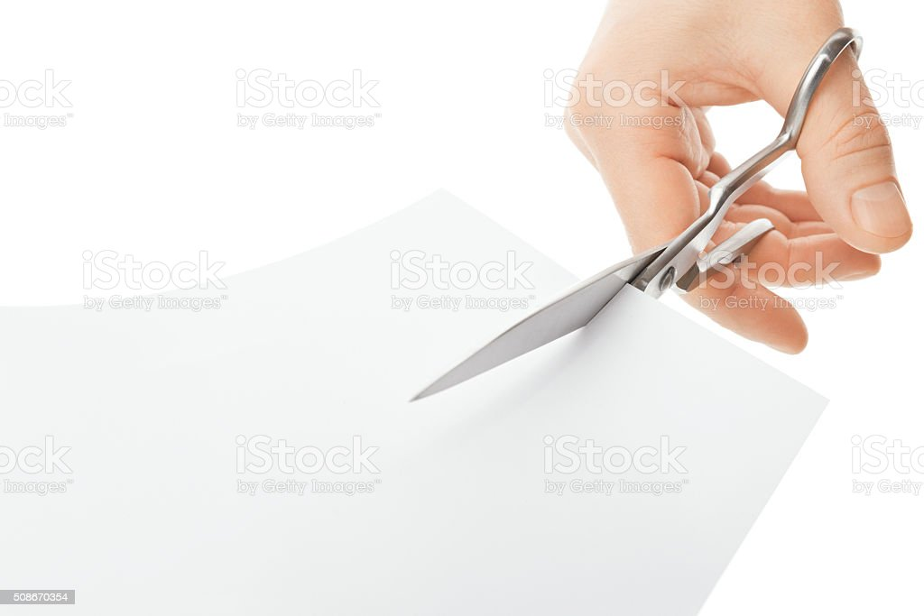 Hand with scissors cutting a white sheet of paper stock photo