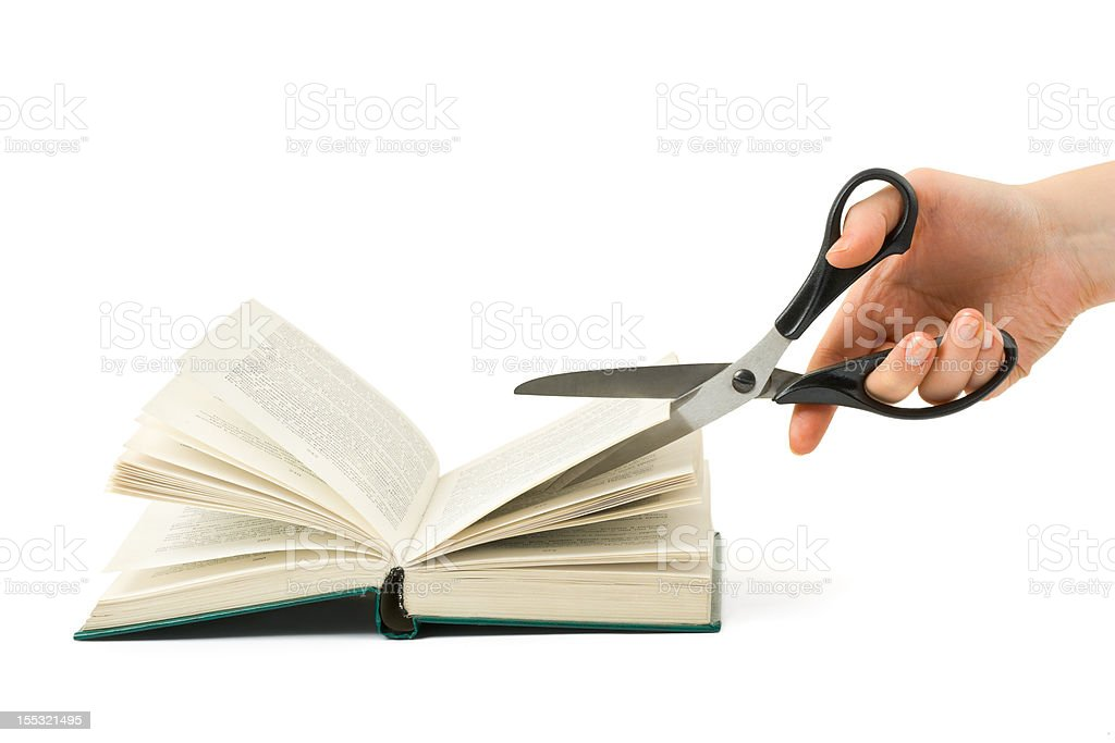 Hand with scissors cutting book royalty-free stock photo