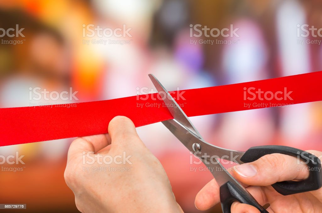 Hand with scissors cutting red ribbon - opening ceremony stock photo