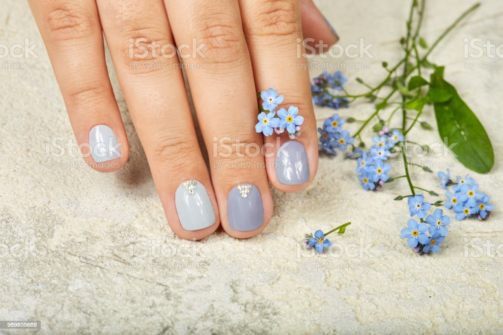 Hand with short manicured nails colored with gray nail polish...