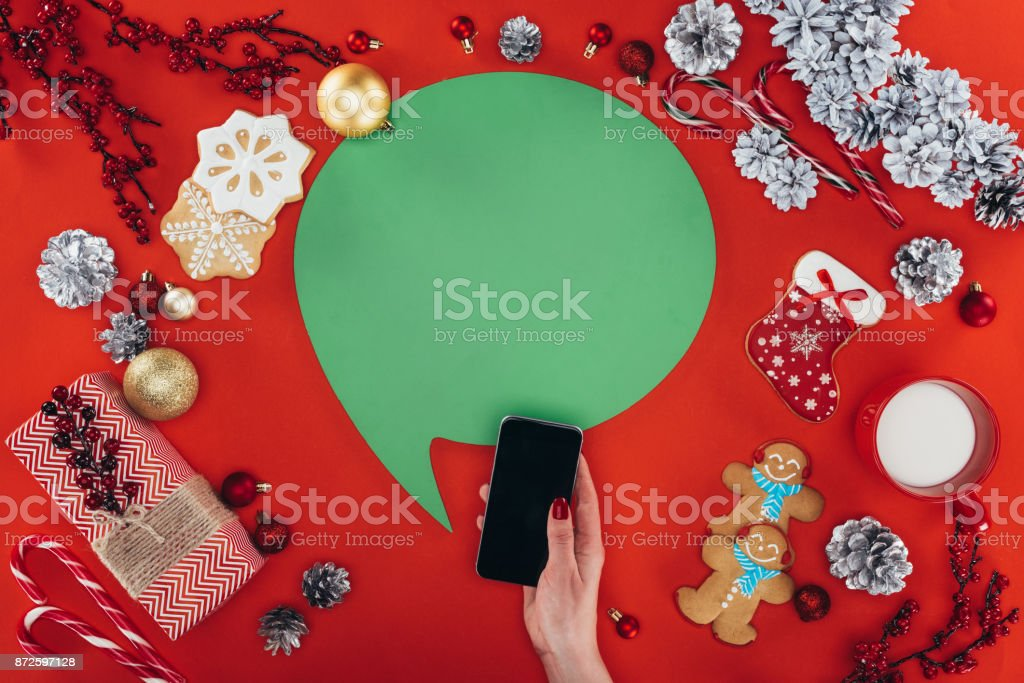 hand with smartphone and christmas speech bubble stock photo