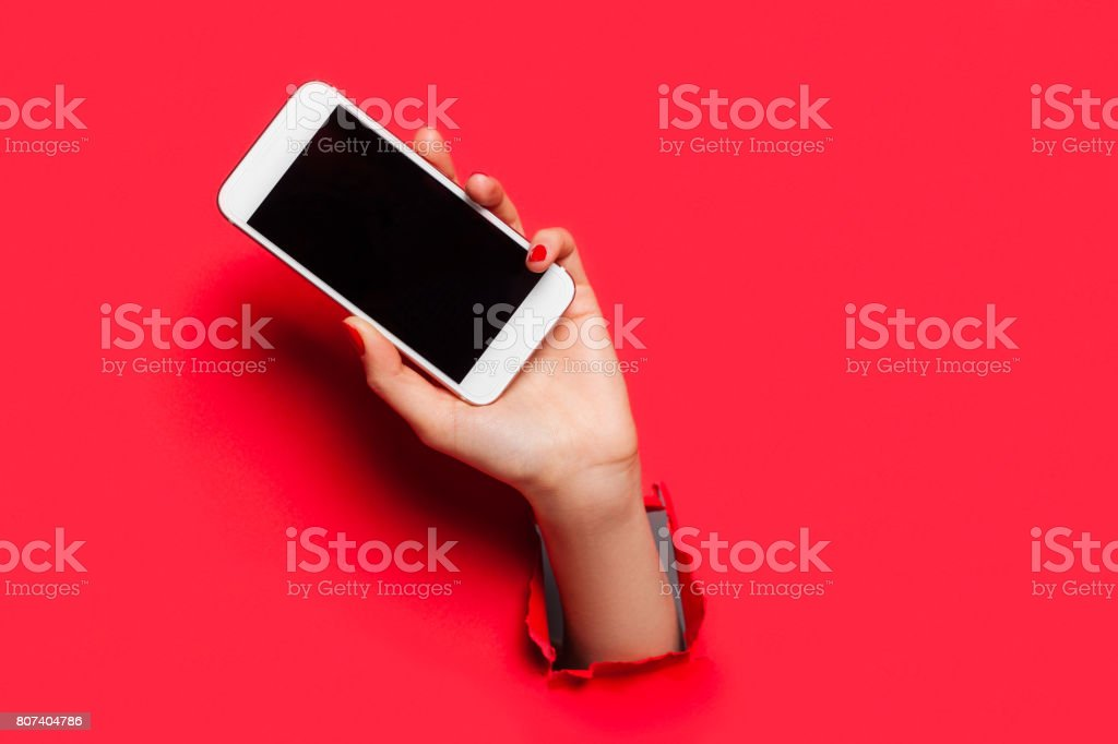 Hand with smartphone on red stock photo