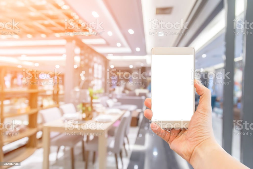 hand with smartphone with blur background image of shopping mall or department store with bokeh and people background usage concept stock photo