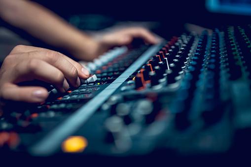 Hand with sound recording studio mixer