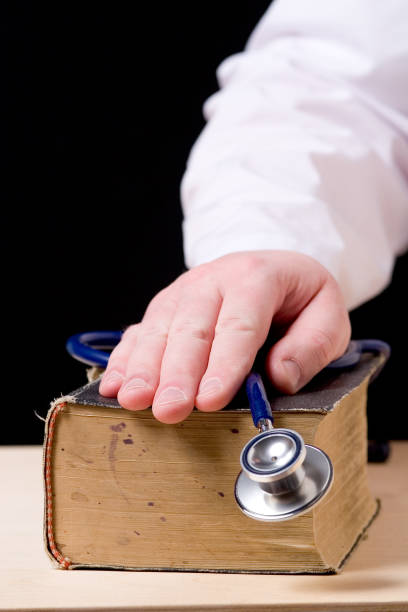hand with stethoscope on top of old book stock photo