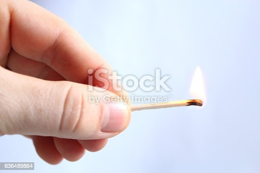 istock Hand with struck match 636489864