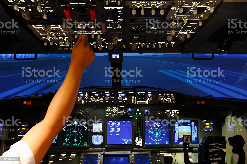 Hand with switch on top of cockpit in flight simulator stock photo