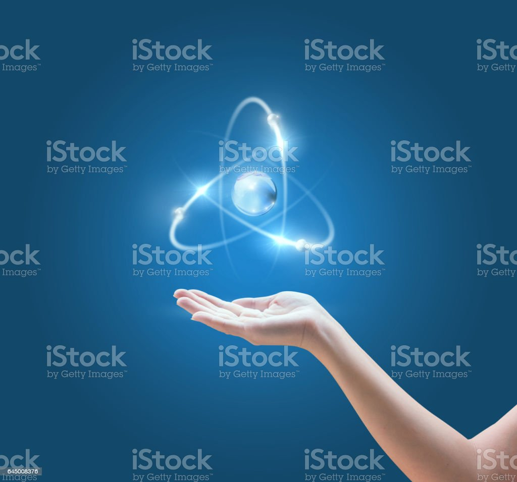 Hand with the atom image on blue background. stock photo