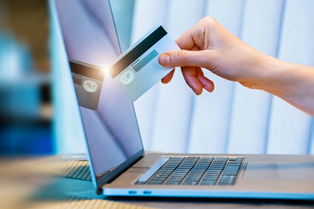 hand with the credit card touches the laptop monitor stock photo