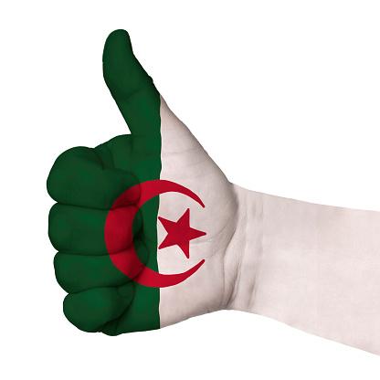 Hand with thumb up, Algeria flag painted as symbol of excellence, achievement, good - isolated on white background
