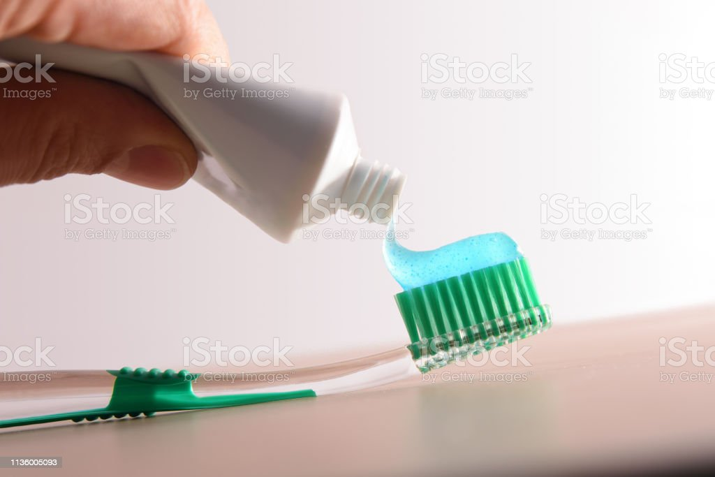 Hand with tube putting toothpaste in a green brush stock photo