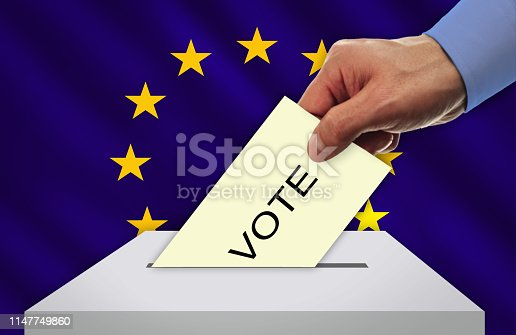 1126684642 istock photo Hand with voting ballot and box in front of the EUROPEAN UNION flag. 1147749860