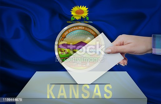 istock Hand with voting ballot and box in front of the flag KANSAS - USA 1159444675