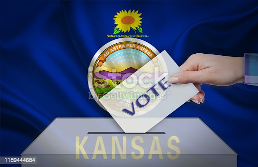istock Hand with voting ballot and box in front of the flag KANSAS - USA 1159444684