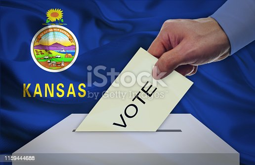 istock Hand with voting ballot and box in front of the flag KANSAS - USA 1159444688