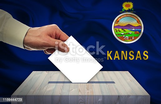 istock Hand with voting ballot and box in front of the flag KANSAS - USA 1159444723