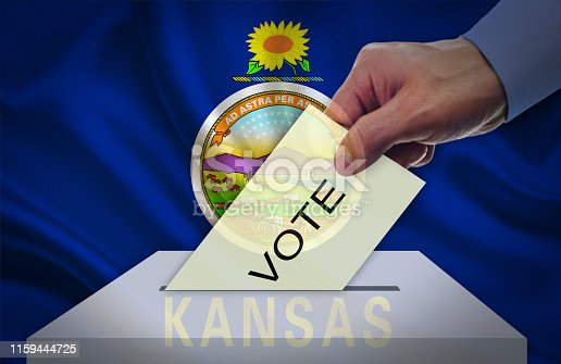 istock Hand with voting ballot and box in front of the flag KANSAS - USA 1159444725