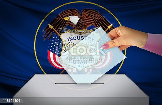 istock Hand with voting ballot and box in front of the flag UTAH - USA 1161241041