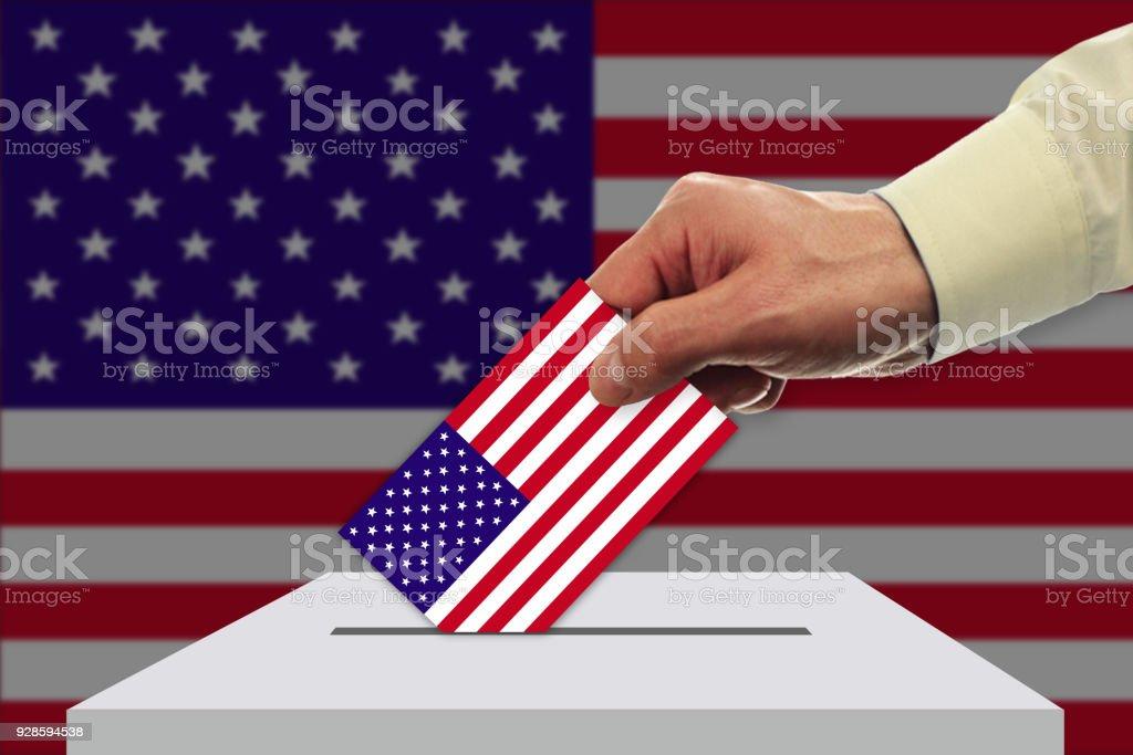 Main avec bulletin de vote et boîte sur le drapeau des États-Unis - Photo