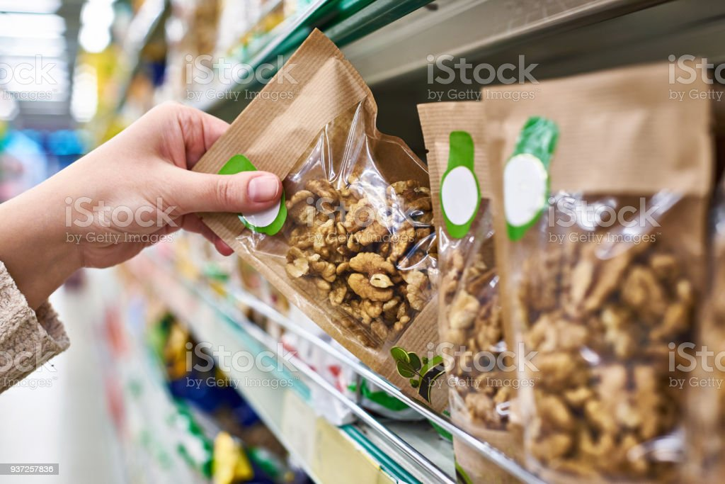 Hand with walnut packaging in store stock photo