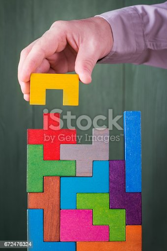 istock Hand with wooden toy blocks. 672476324