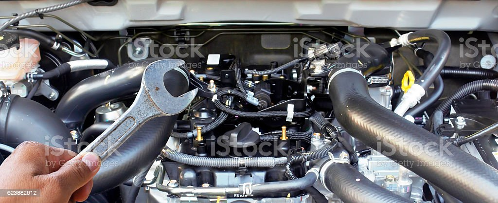 Hand with wrench checking car engine. stock photo