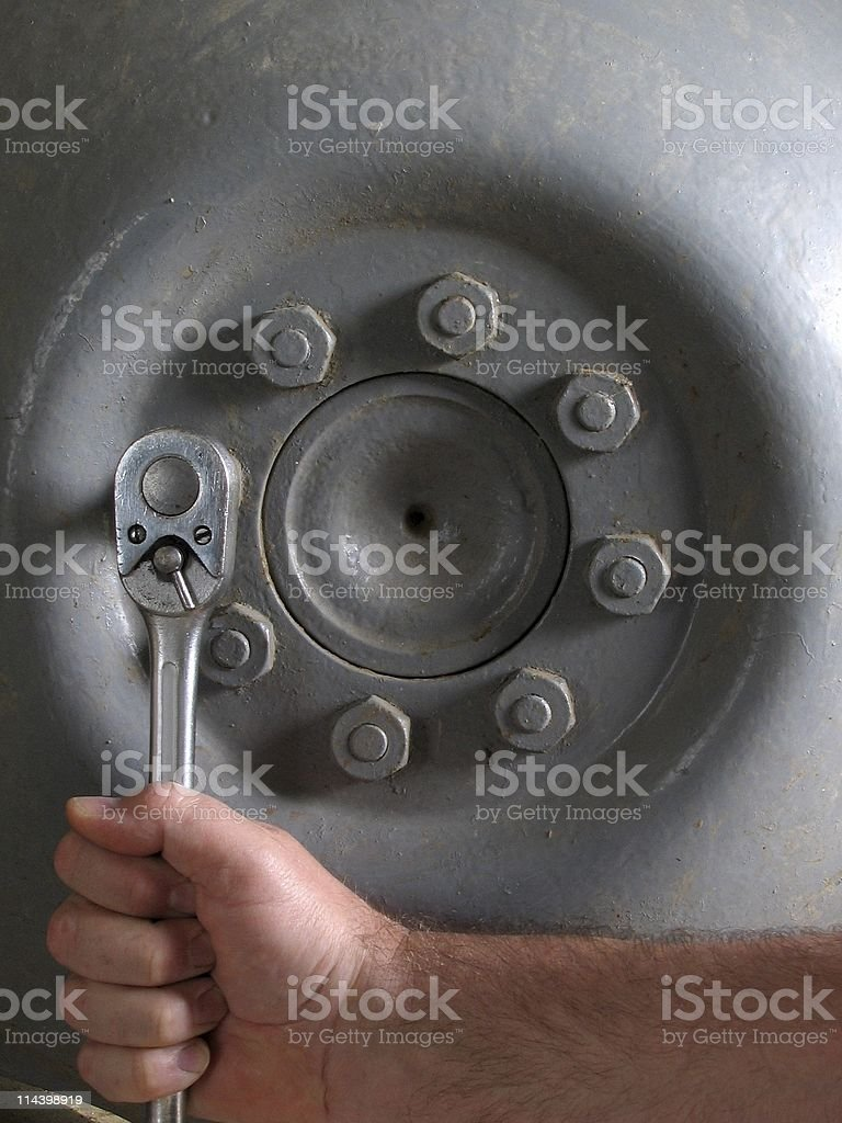 Hand With Wrench Working On Tractor Wheel Nuts stock photo