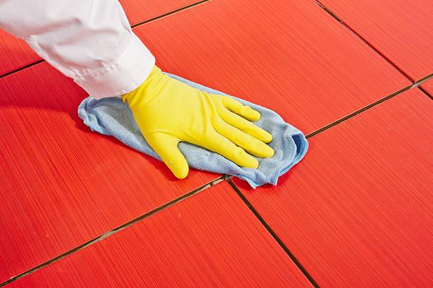 hand mit gelbe handschuhe - fliesenkleber stock-fotos und bilder