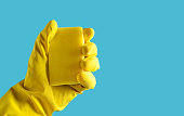 Hand with yellow rubber glove holds a sponge on a blue background, copy space