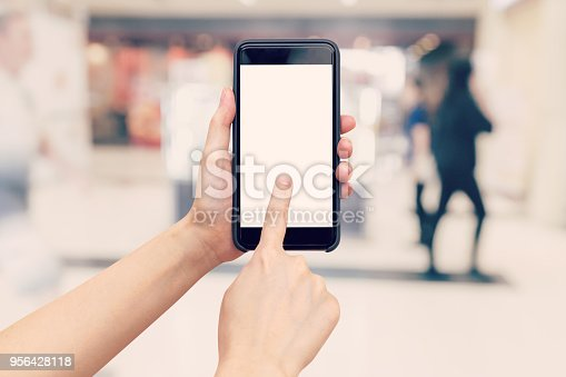 890476604 istock photo Hand woman holding and using phone with blurred background in shopping mall. 956428118