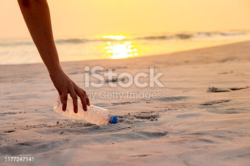 Hand woman picking up plastic bottle cleaning on the beach , volunteer concept.