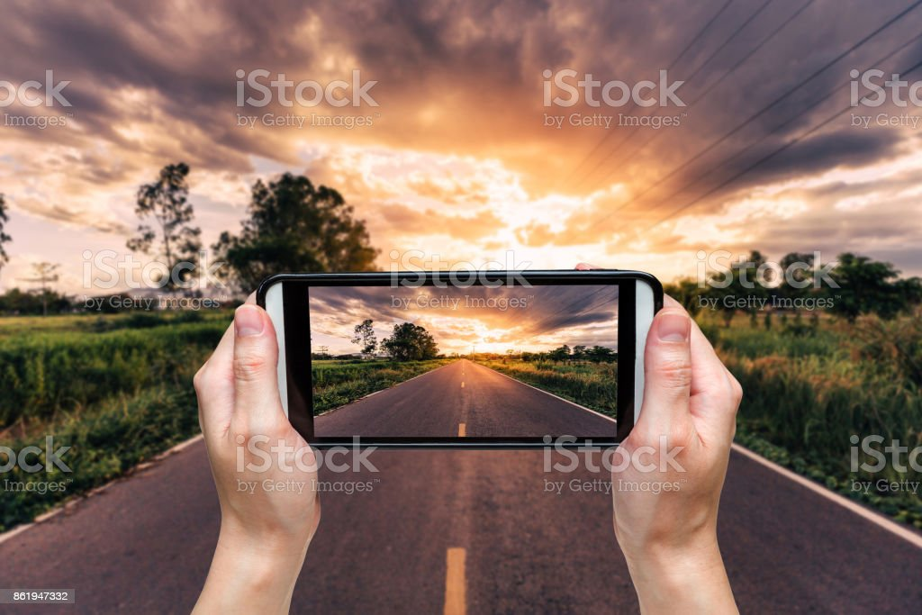 hand woman taking photo at road and sunset. stock photo