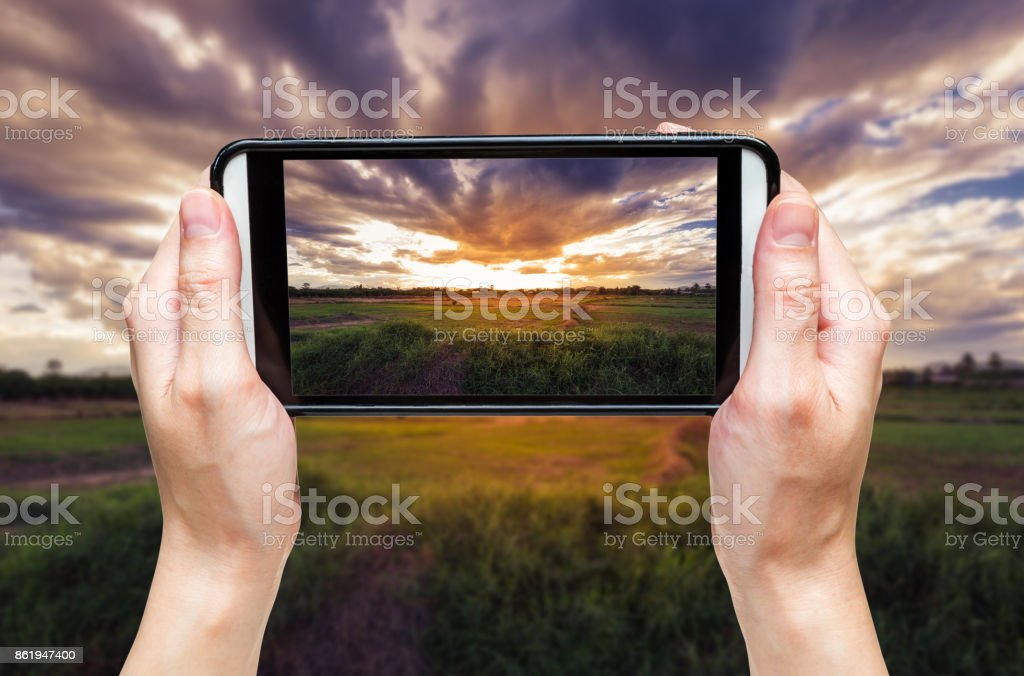 hand woman taking photo at sunset. stock photo
