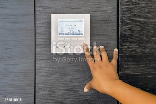 996279800istockphoto hand woman turns on air conditioning 1174518916