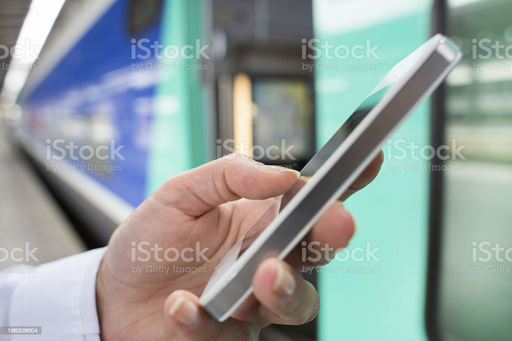 Hand woman using her cell phone in station platform royalty-free stock photo