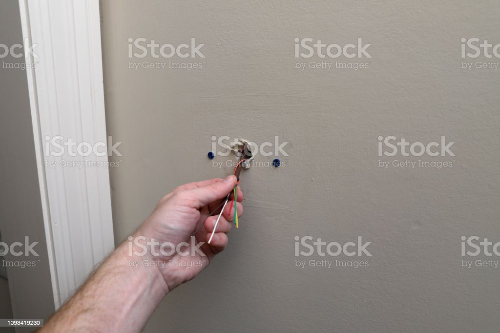 hand works on control wire for air conditioner thermostat stock photo