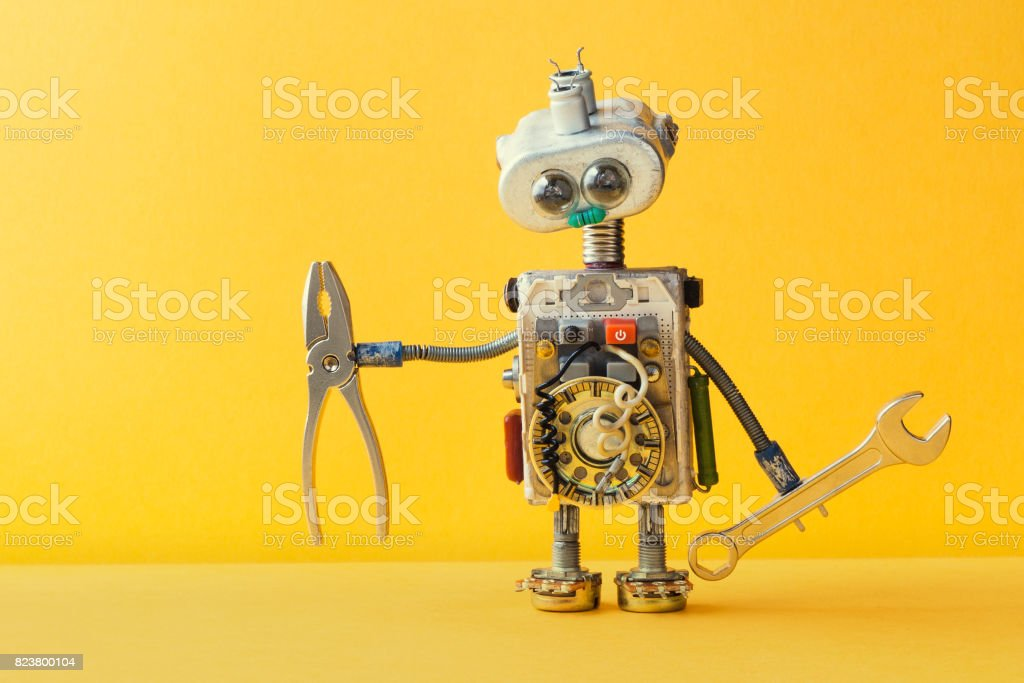 Hand wrench pliers robot handyman on yellow background. Cyborg toy lamp bulb eyes head, electric wires, capacitors vintage resistors stock photo