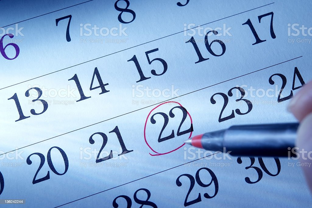 Hand writing a red round mark of a calendar stock photo
