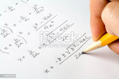 A hand writing out algebra equations.