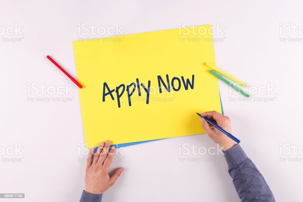 Hand writing Apply Now on yellow paper stock photo