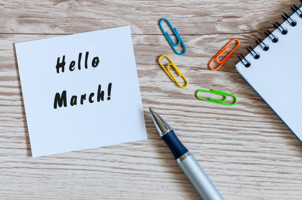 hand writing hello march on piece of paper near office suplies at wooden table. beginning of spring concept - welcome march stock photos and pictures