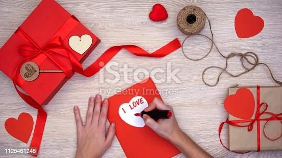 1125461272 istock photo Hand writing I love you phrase on greeting card lying on table with gift boxes 1125461248