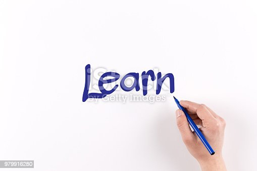 istock Hand writing Learn on white paper, View from above 979916280