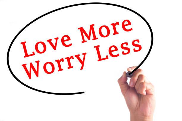 hand writing love more worry less on transparent board - danke zitate stock-fotos und bilder