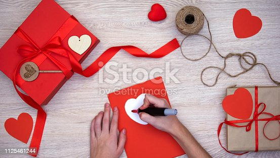 1125461272 istock photo Hand writing love word on greeting card lying on table with craft gift boxes 1125461244