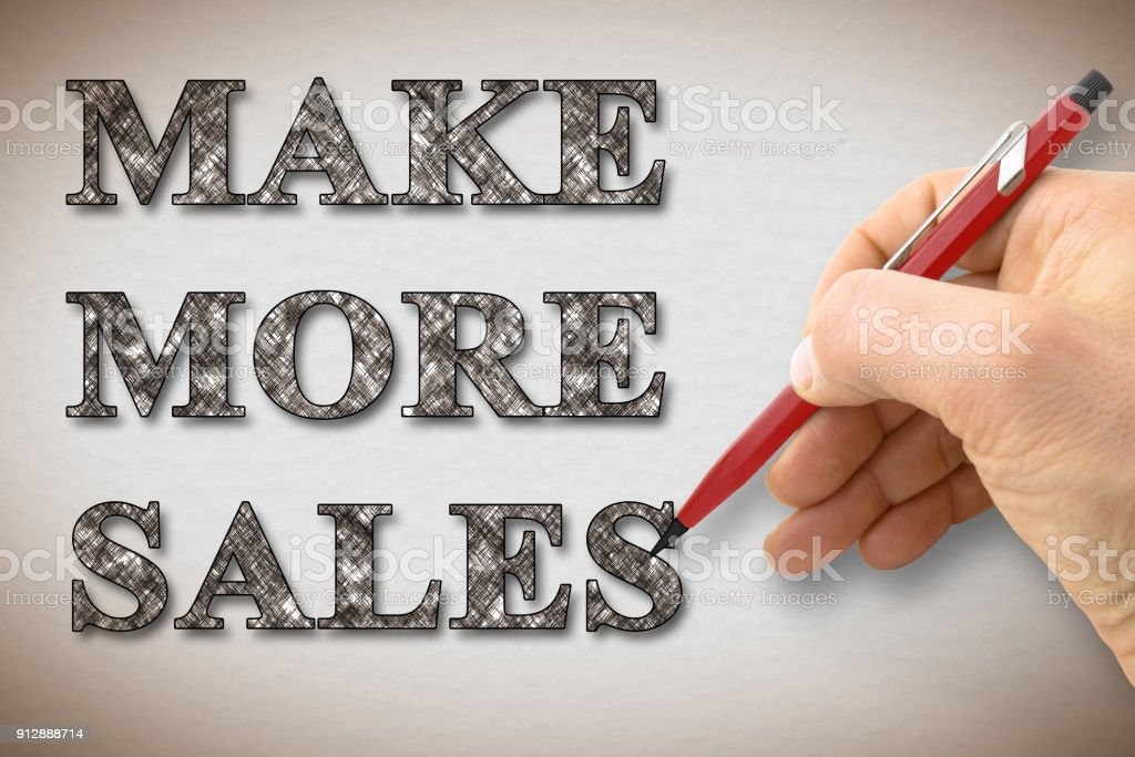 Hand writing 'Make More Sales' on a blank card - concept image stock photo