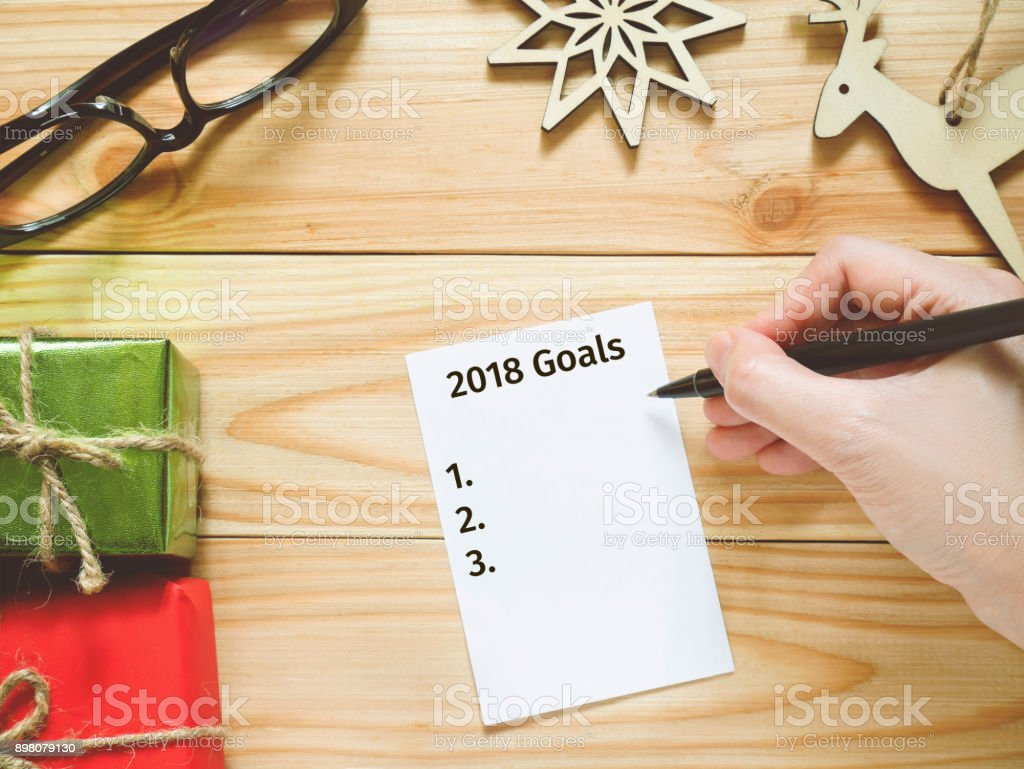 Hand writing New Year's Resolutions on paper