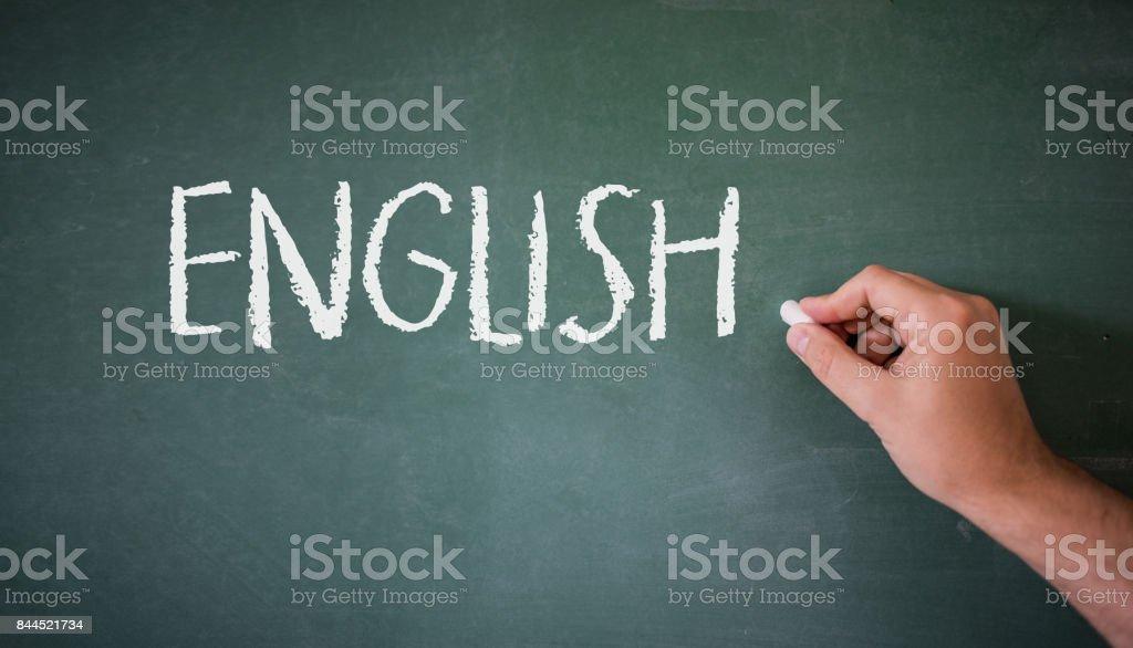 Main qui écrit sur un tableau noir dans une classe de langue avec le mot «Anglais» a écrit. - Photo