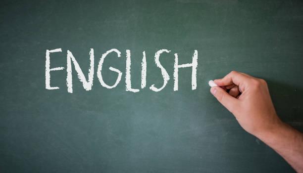 main qui écrit sur un tableau noir dans une classe de langue avec le mot «anglais» a écrit. - langue anglaise photos et images de collection