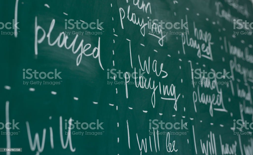 Hand writing on a chalkboard in an language english class. Hand writing on a chalkboard in an language english class Blackboard - Visual Aid Stock Photo